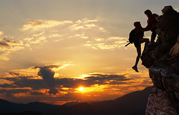 two men climbing rocks at sunset