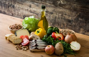 Mediterranean diet. Fruit,vegetables, grain, nuts olive oil and fish on wooden table