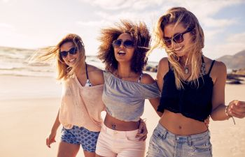 Three energetic happy women spending time together on a beach.