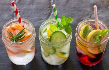 three jars with hydrating water with fruits,